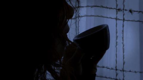 woman in sorrow stands pensively near a closed window, in the dark Footage