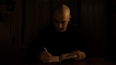 bald theater director takes notes on his diary after a rehearsal Footage