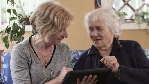 Daugther explains to her mother how works a tablet Footage