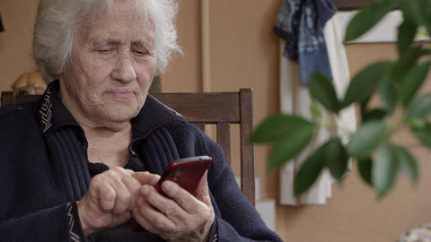 Elderly lady texts messages with smartphone Footage