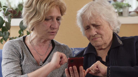 Patient daughter explains to her old mother how to use smartphone Footage