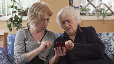 Daughter explains to her old mother how works smart phone Footage