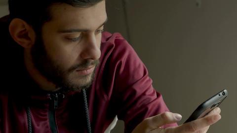 bearded guy with hoodie fleece textmessaging Footage