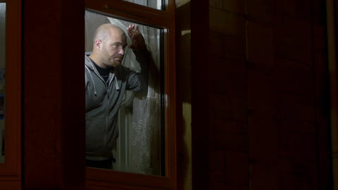 man at home leans at a window and waits for his lover coming, looking concerned Footage