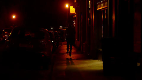 slow motion of a man running on a dark sidewalk to escape from followers Live Action