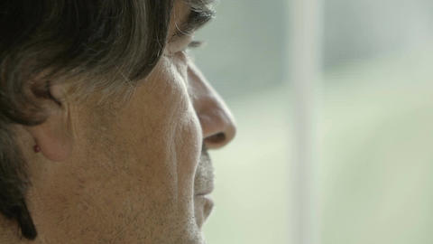 grizzled hair man looking pensively out of the window Footage