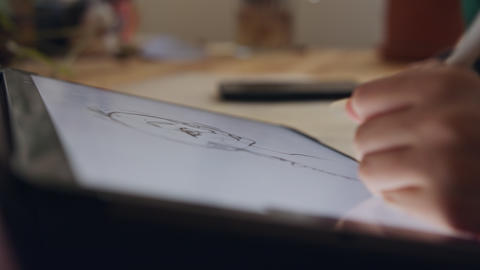 Teenage girl drawing using a tablet computer and an electronic pen Live Action