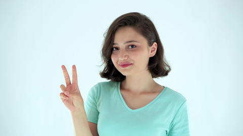 Young woman showing victory or peace sign on white background. Cheerful girl showing two fingers Live Action