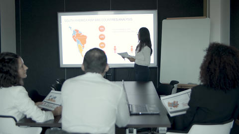 Young businesswoman explaining countries analysis to managers Live Action