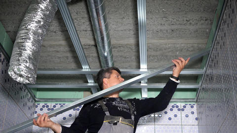 Professional worker fasten ceiling profiles in new flat bathroom Live Action