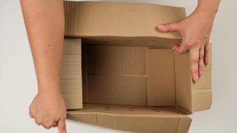 female hand opens brown cardboard box and fills with white filler for safe transportation Live Action