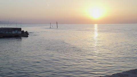 Sun rise on the sea pier. Calm morning sea. Fishing rods on the pier. Bright sun Live Action