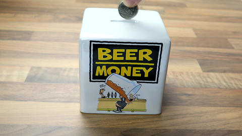 Money Box For Saving Money. British coin being out into a funny beer money piggy bank Live Action