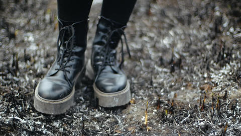 Close-up front shot of walking legs in black stylish boots on burnt grass of Live Action