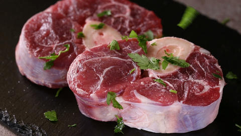 Spreading fresh green parsley on one piece of raw fresh beef shank Live Action