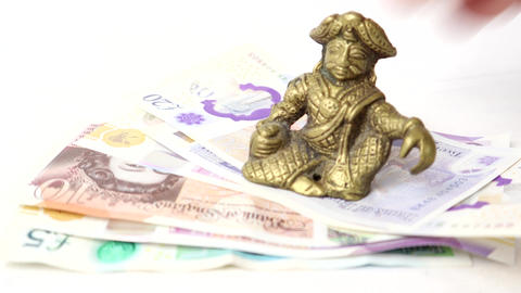 English Banknotes With A Good Luck Paperweight Placed On Top Live Action