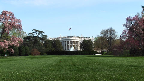 The camera zooms-in across a lush green yard to the entrance of the White House Footage