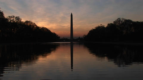 The Washington Monument in seen in silhouette and also in the Reflecting Pool Footage