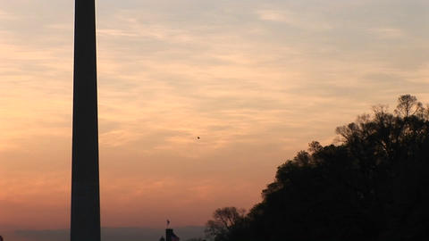Upward pan of the Washington Monument, silhouetted against a golden sky Footage