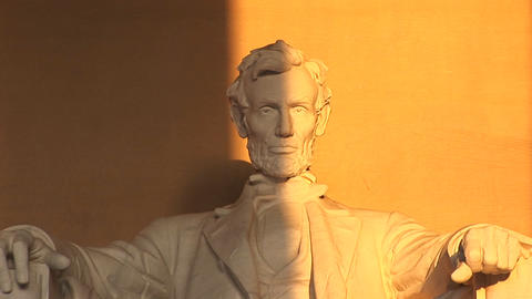 President Lincoln's sculpted face is seen half in shadow, the other half bathed in golden light Footage