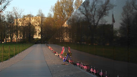 In front of the Vietnam Veterans Memorial Wall, ribbons on tributes and mementos flutter in the bree Footage