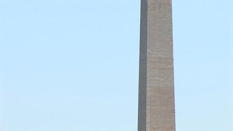 The Washington Monument is flanked at the base by blossoming cherry trees and as the camera pans-up Footage