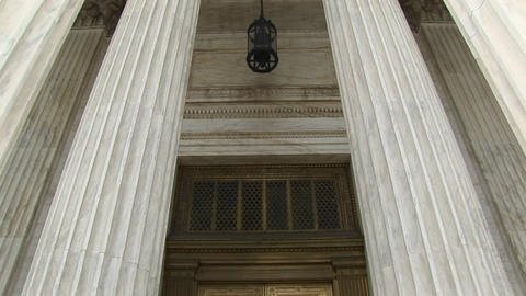 View of columns, a hanging lamp, and bronze doors at the west entrance of the Supreme Court Live Action