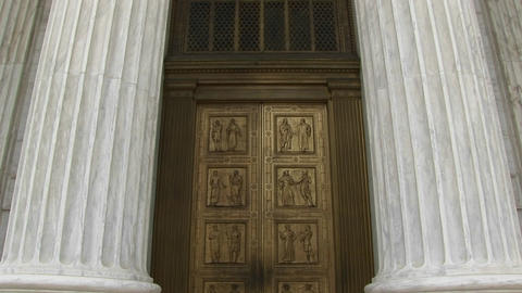 View of columns, a hanging lamp, and bronze doors at the... Stock Video Footage