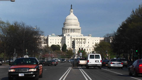 Traffic flows in many directions in front of the United States Capitol Building Footage