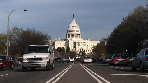 View tracks-in on the United States Capitol Building in the background of streets flowing with traff Footage