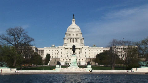 Camera zooming across the Reflecting Pool and focusing on the exterior of the U.S. Capitol building Footage