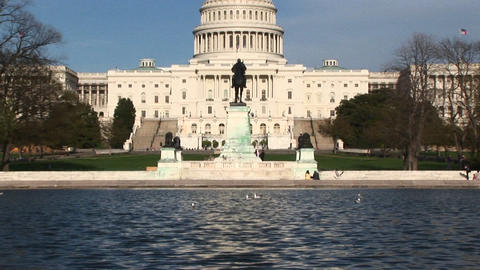 Panning up from the Reflecting Pool in Washington, DC and focusing on the U.S. Capitol building Footage