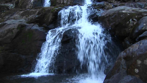 The camera pans up a waterfall Stock Video Footage