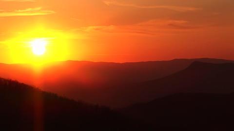 Pan left across a fiery golden-hour sky above a mountain... Stock Video Footage