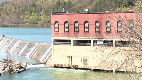 Camera pans left passed an old mill built alongside a dam... Stock Video Footage