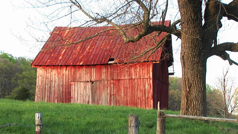 Faded red roof and siding of an old barn reflects the passing of the family farm and an entire era Footage