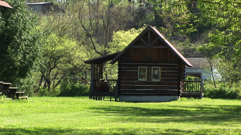 A small, rustic log cabin sits surrounded by idyllic country scenery Footage