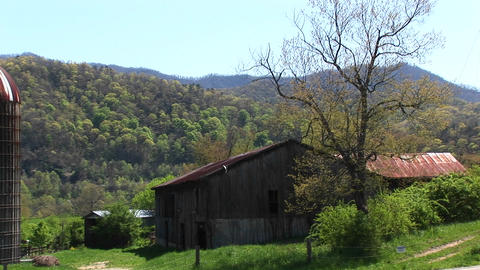 A country house and barn sit surrounded by beautiful mountain scenery Footage