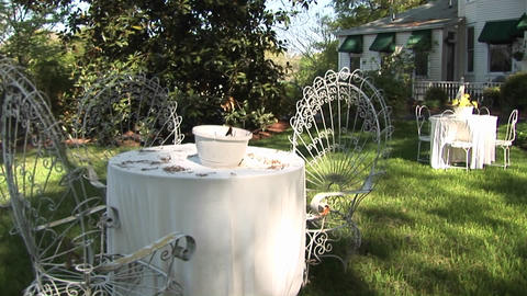 Whimsical tables and chairs furnish the yard of a... Stock Video Footage
