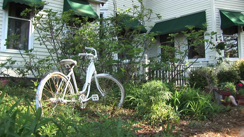 Camera pans up from a vintage bicycle in a garden towards... Stock Video Footage