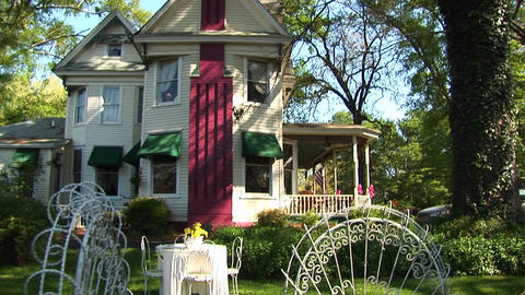 Tables and chairs furnish the yard of a Victorian home... Stock Video Footage