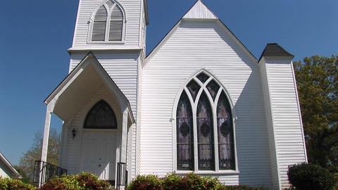 The white clapboard exterior of an old country church is set against a blue sky in this panning shot Footage