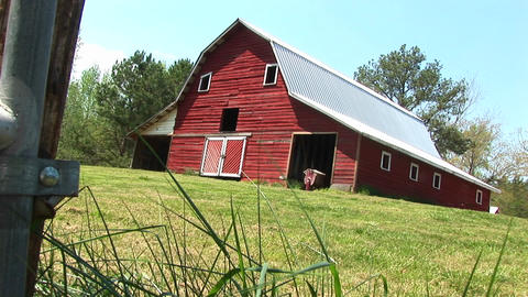A lovely, old red barn sits on top of a hill Footage
