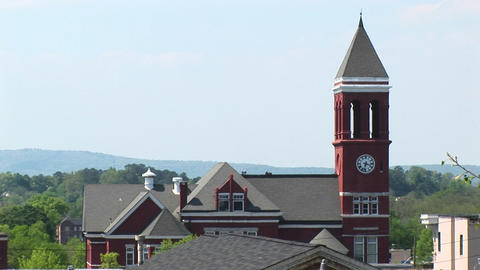 An old clock tower stands tall above the town's rooftops Stock Video Footage