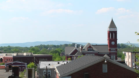 The camera pans-right across the roofline of a small town to highlight an old clock tower Footage