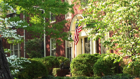 An American flag, seen through the trees, hangs proudly beside a home's doorway Footage
