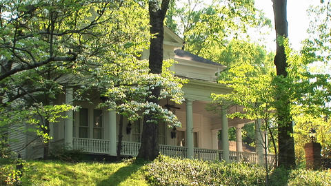 A medium-shot of a lovely old white house hidden in the trees Footage