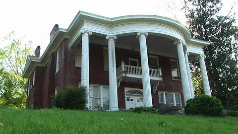 Massive, Stately Columns Rise To Meet The Rounded Curve Of This Classical Revival Style Home stock footage