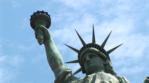 The Statue of Liberty, with torch held high, stands against a blue sky full of wispy clouds Footage