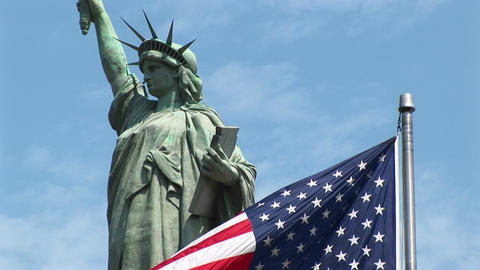 The Statue of Liberty stands majestically against a blue... Stock Video Footage